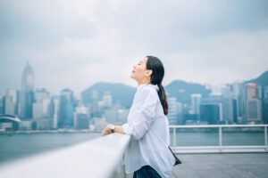 woman outside in the city overlooking water is finally free from stress at work